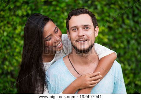 Closeup of smiling young Asian woman embracing Caucasian boyfriend from behind with green leaves wall in background. Man is looking at camera. Front view.