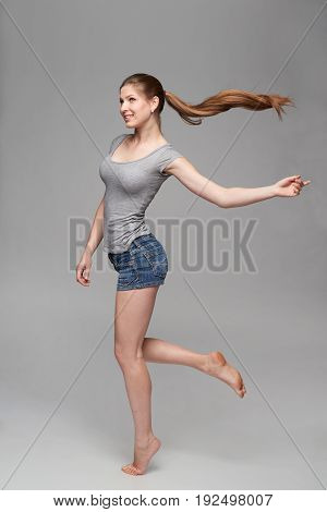 Beautiful barefooted full length female in denim shorts and grey tshirt jumping over grey background with hair ponytail flying in air