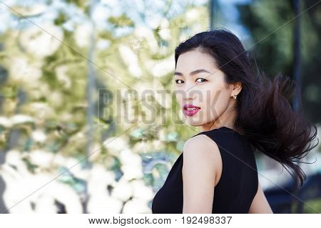 Asian young woman against the mirror wall outdoors