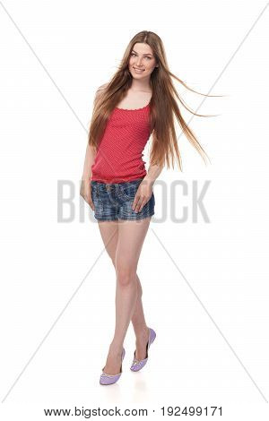 Full length of smiling leggy young female in denim shorts and red top with beautiful long hair, isolated on white background