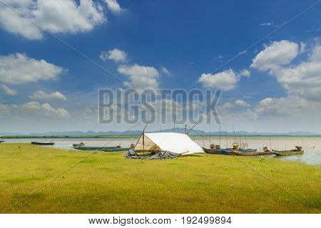 White Tent and Longtail Fishing Boat in Camp of Fisherman beside Lake of Lam Takong under the Cloudy Blue Sky in Nakhon Ratchasima Thailand.