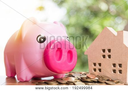 real estate investment wood house model with coin savings plans for housing blur background financial concept