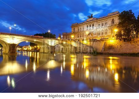 The Palace of Justice and bridge Ponte Umberto I with mirror reflection seen from the Tiber riverside during morning blue hour in Rome, Italy