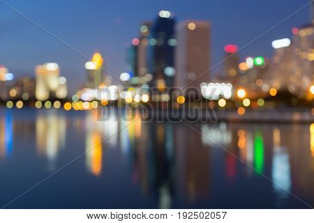 Night blurred bokeh light office building with reflection at twilight abstract background