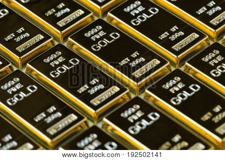 closed up shot stack of shiny gold bars as business or financial investment and wealth concept.