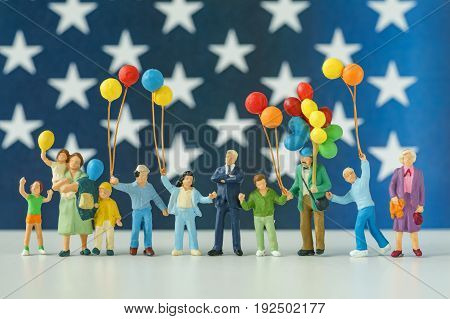 miniature figure happy american family holding balloon with USA stars flag in the background as celebrating the Independence day.
