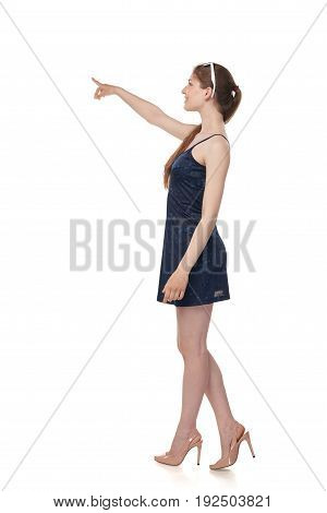 Beautiful casual young woman isolated on white background in full length standing in profile pointing or pushing something with index finger.