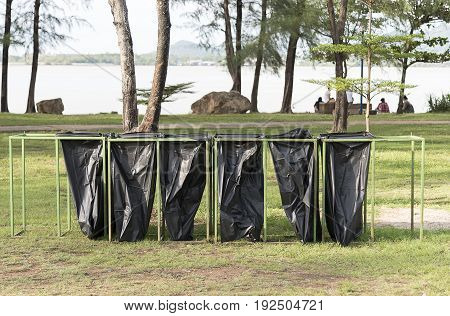 six Black garbage bags on the park