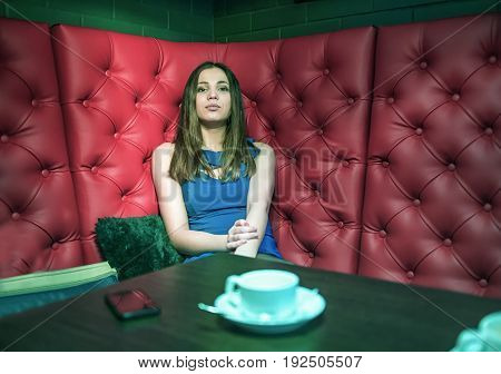 Girl sitting in a cafe on red sofa