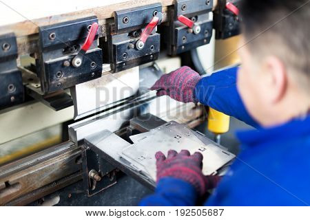 young worker runs automation equipment in manufacturing factory