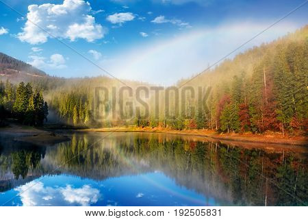 rainbow over the picturesque lake in foggy spruce forest. majestic autumn sunrise in gorgeous landscape with beautiful weather