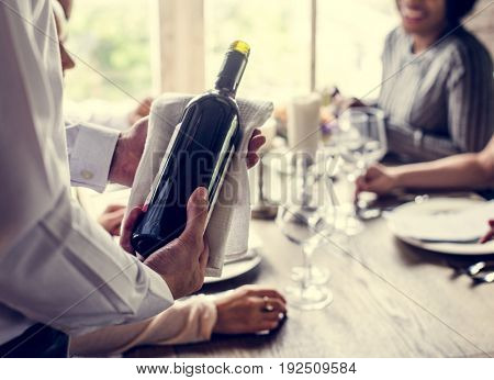 Waiter serving wine to the customers