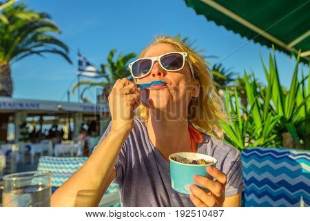 Healthy Mediterranean diet. Blonde caucasian female eating healthy food outdoor. Europe summer vacation. Lifestyle woman eating typical Yogurt Greek in Koroni, Peloponnese, Greece. Summer holidays.