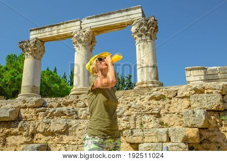 Young happy tourist drinks orange juice at Archaeological Site of Ancient Corinth in Greece. Young woman holding refreshing drink while visiting Temple of Ottavia in hot day. Tourism travel concept.