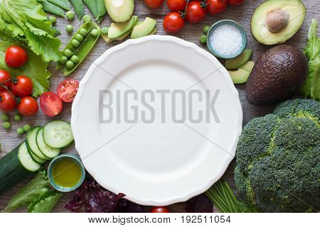 Ingredients for the salad, fresh tomatoes, cucumber, avocado, lettuce, spring onion, broccoli on the grey wooden table, copy space for text, top view, selective focus