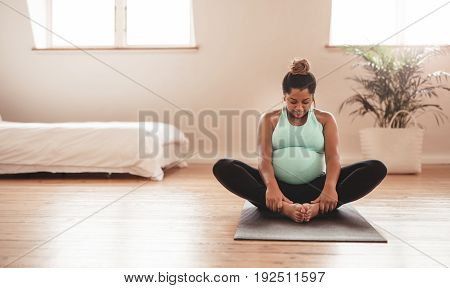 Beautiful Expectant Mother Doing Yoga At Home
