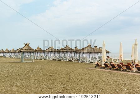 Equipped with tents with thatched roofs deserted beach on a cloudy day. The offseason