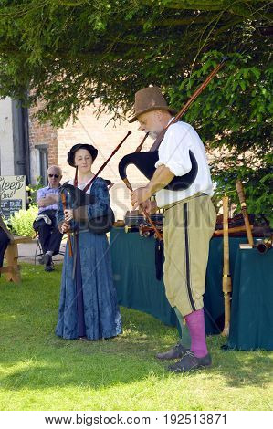 Congleton; Cheshire; England United Kingdom - June 17 2017 : Little Moreton Hall Tudor musicians playing bagpipes