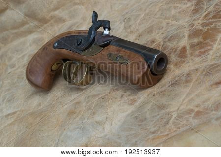 An old time black powder pistol sits on top of the back side of a deer hide
