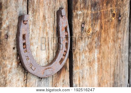 Old rusty horseshoe on wooden natural background. Symbol of luck and happy fortune. Lucky charms