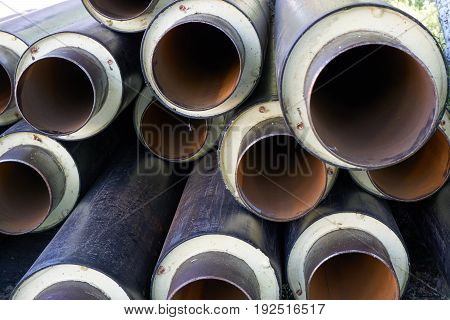 close up shot of a pile stack of big metal pipes tubes with heater isolation insulation and pvc shell at construction site