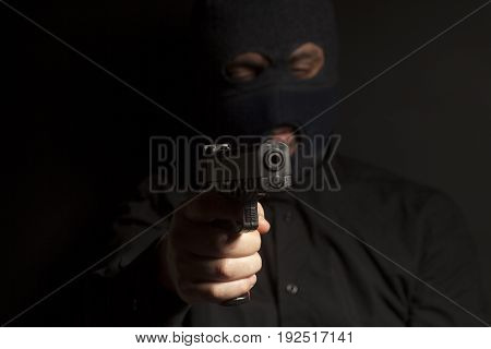 criminal bandit man wearing in balaclava holds a gun in his hand on black background