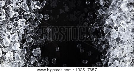 Pieces of crushed ice cubes on black background. Copy space, top view