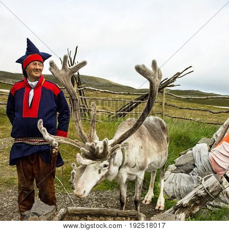 Honningsvag, Norway - May 3, 2017: Deer and reindeer breeder dressed in national clothes the Sami in the area of town Honningsvag.