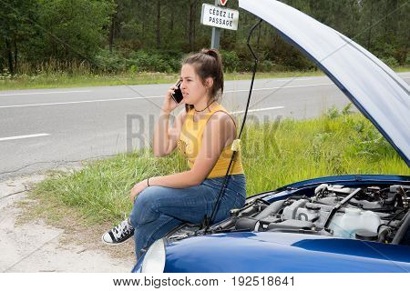 Fashionable Young Woman Phoning For Help On Her Mobile As She Leans Against Her Car Which Has Broken