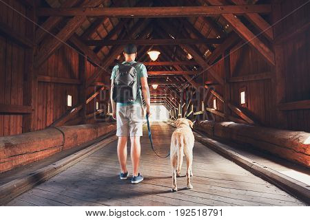 Young tourist with his dog inside of the covered bridge over the river in Radosov Czech Republic