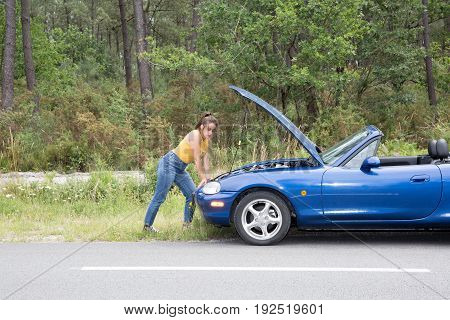 Young Caucasian Woman With Brown Hair Under The Hood Of Her Car Break Down