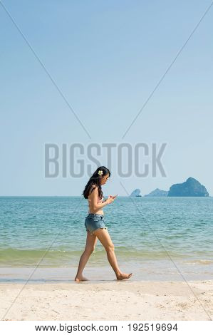 Girl Looking At Smart Phone And Walking On The Beach
