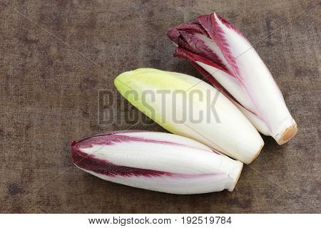 mixed fresh yellow and red chicory on a grungy background