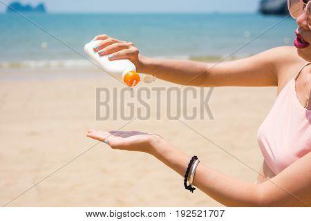 Girl Applying Sun Lotion On The Beach