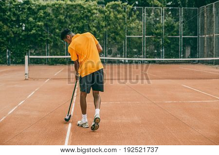 A young man in a sports uniform is cleaning a tennis court. The tennis player is preparing a court for the game.