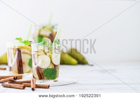 Refreshing Drink With Pear, Cinnamon On White Table. Copy Space