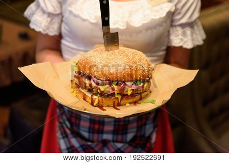 Unrecognizable waitress standing and holding hamburger served with knife.