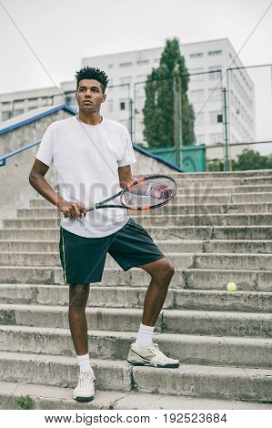 Tennis is his passion. Confident young man in sports clothes carrying tennis racket and looking away while standing against grey background.