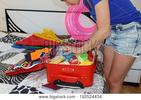 The girl in collects things for the ride. Getting ready for travelling to the sea. Young woman packing suitcases on floor at home