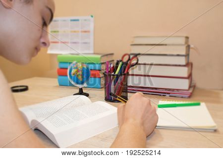 Girl doing her homework. School books on desk education concept. Young Student Girl doing lessons at home