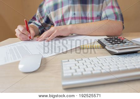 Businessman working on office desk with Calculator a computer a pen and document. Businessman signs a document