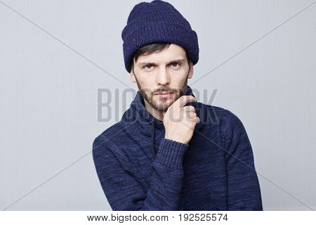 Portrait of suspicious pensive young Caucasian male in casual sweater touching face while thinking over something trying to come up with solution having perplexed and puzzled expression. Human emotions concept.
