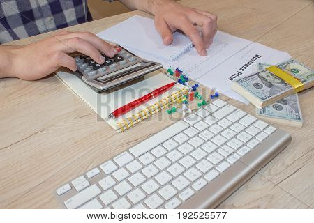 Businessman working on office desk with Calculator. accounting concept. Financial report values with dollars calculator