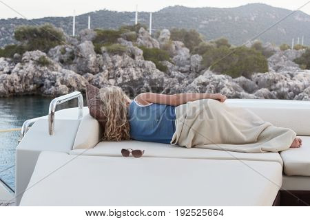 Mature blond haired woman is relaxing after interesting day on the sofa of luxury yacht floating in the sea. Tired and happy female sleeping on open air.
