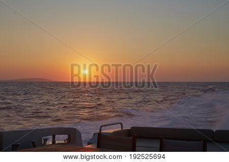Yacht sailing passing by beautiful sunrise. Fresh and sailty air is all around. Warm colors. Sailboat. Yachting. Travel Concept. Vacation