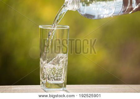 In the glass water flows from the bottle on the nature on a wooden board