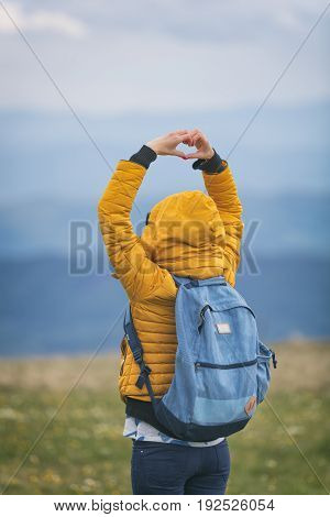 Girl making a heart-shape with mountain landscape in the background.