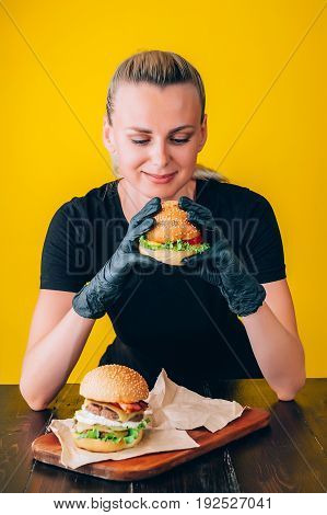Bright juicy appetizing burgers with a cutlet cheese marinated cucumbers tomatoes and bacon in the hands of a girl a girl in special gloves for burgers
