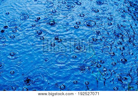 Rain Drops On The Surface Of A Street Road On A Rainy Day, Toned Blue