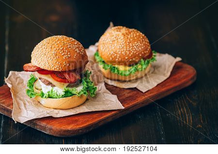 Bright Juicy Appetizing Burgers With A Cutlet, Cheese, Marinated Cucumbers, Tomatoes And Bacon In Th